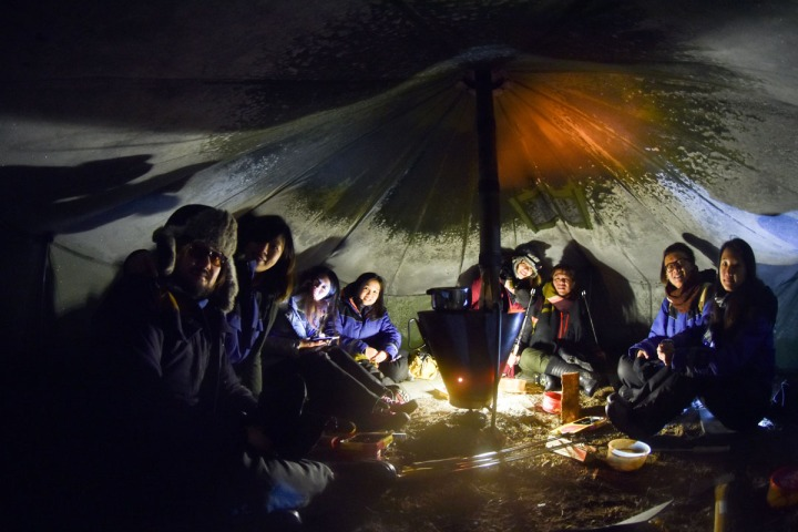 02.極光攝影團的成員在帳蓬內升火取暖,等待極光出現。