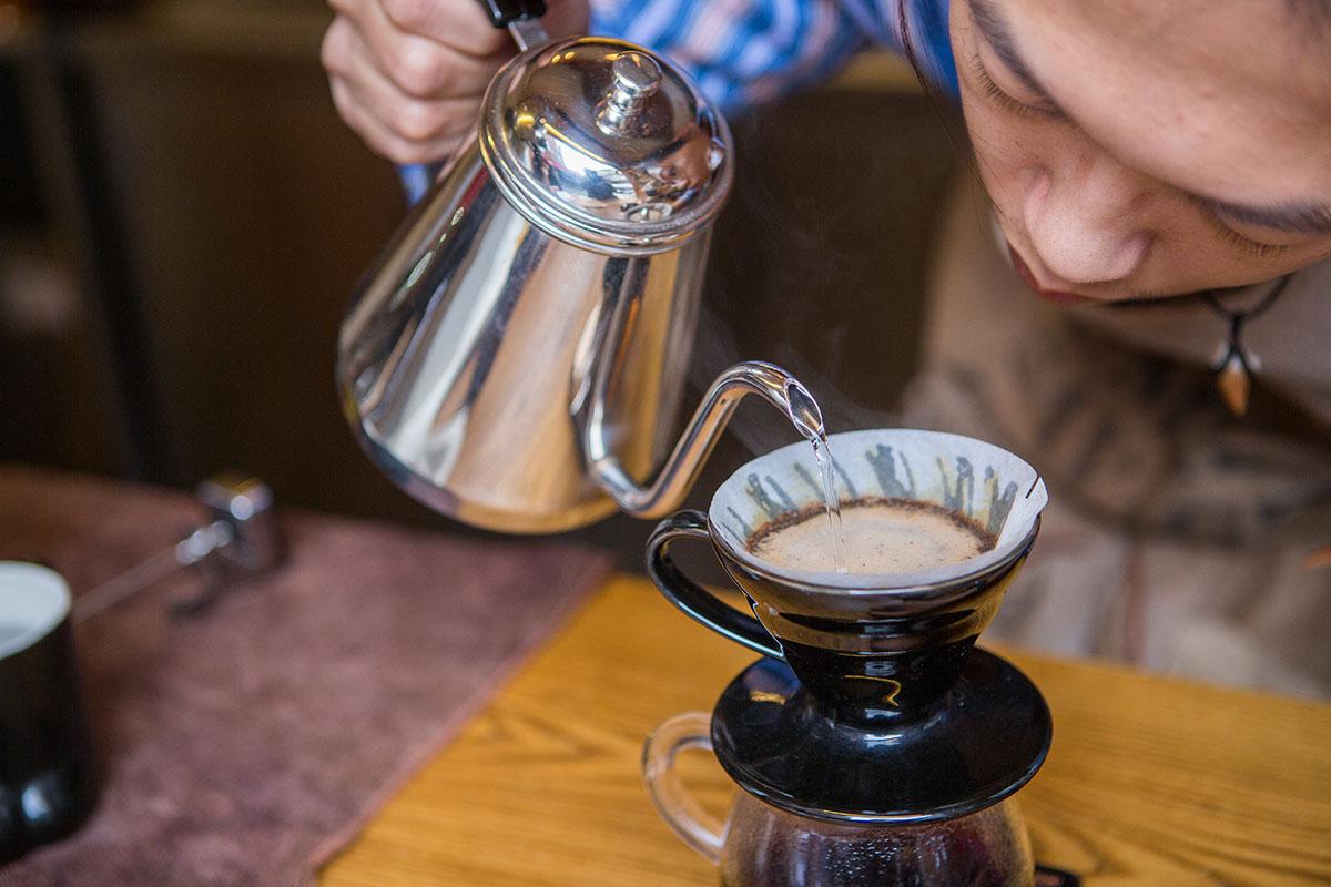 01.邱三歲在吧台沖煮咖啡時非常專注。